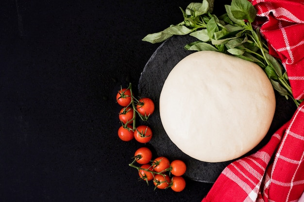 Round freshly bread dough; cherry tomatoes; basil and napkin on black background