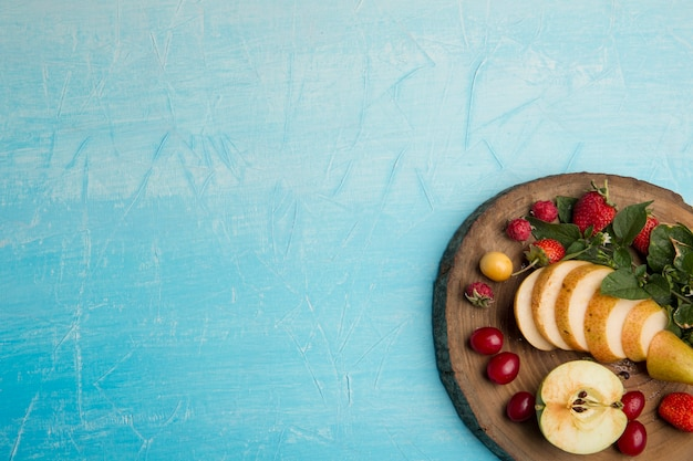 Круглая тарелка фруктов с грушами, яблоками и ягодами в углу