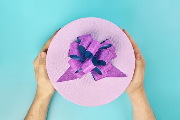手に弓を持つ丸いギフトボックス。青の背景にギフト用の紫色の閉じたボックス。あらゆる休日に贈るパッケージ:誕生日、バレンタインデー、クリスマス、記念日、結婚式、その他のお祝い