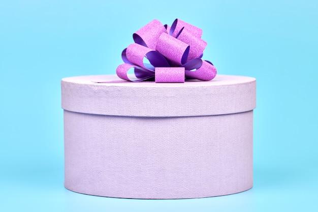弓付きの丸いギフトボックス。青の背景にギフト用の紫色の閉じたボックス。誕生日、バレンタインデー、クリスマス、記念日、結婚式、その他のお祝いのサプライズパッケージ