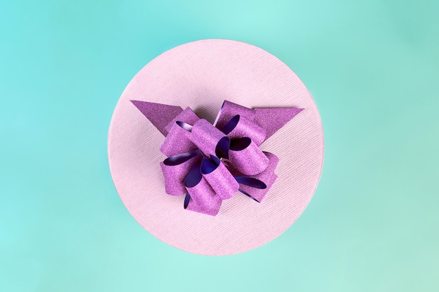 Round gift box with bow, top view. purple closed box for gift on blue background. package for surprise for any holiday: birthday, valentine's day, christmas, anniversary, wedding and other celebration
