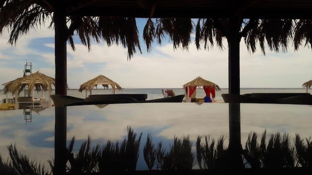 Круглый стеклянный стол, на котором изображены пальмы, море и небо. прекрасный вид на пляж в туристическом городке. летний бар на красном море. беседки с шезлонгами для защиты от солнца.