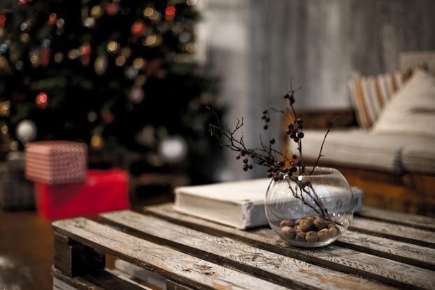 果実と枝と丸いガラスの花瓶がテーブルの上に立つ