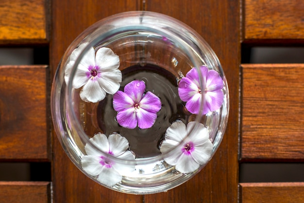 Round glass vase with floating flowers on wooden table