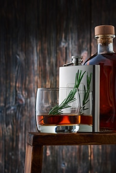 A round glass with a portion of whiskey and a sprig of rosemary