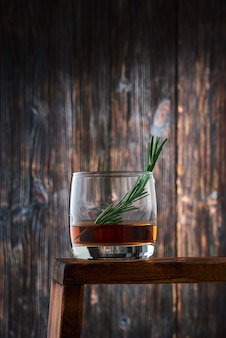 A round glass with a shot of whiskey and a sprig of rosemary