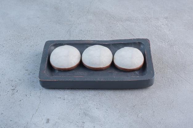 Biscotti smaltati rotondi su banda nera su tavola di pietra.