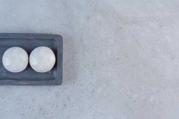 Круглое глазированное печенье на черной тарелке на каменном столе.