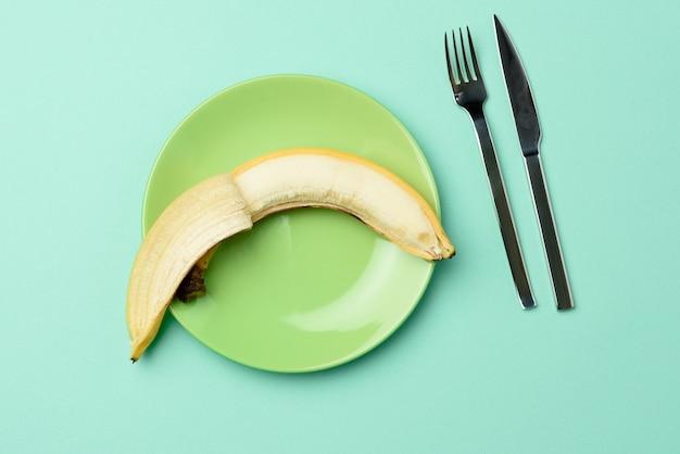 Круглая зеленая керамическая тарелка с целым бананом, ножом и вилкой на зеленом фоне, диета, вид сверху