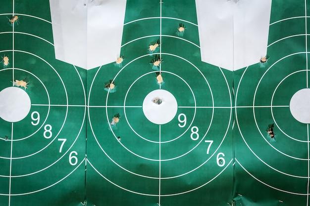 銃弾の穴のある丸い緑色のシューティングターゲットが軍事訓練場にクローズアップ