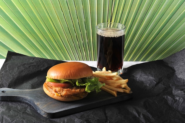 Round hamburger with chicken cutlet and french fries and a glass of coke
