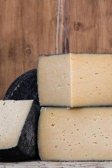 Круглая головка твердого сыра с мелко нарезанным ломтиком на деревянном