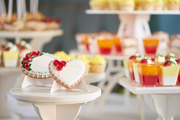 Round and heart shaped glazed cookies, decorated with glaze flowers and pattern are on the wooden stand in the restaurant. there is a colorful delicious candybar behind them. good choice for wedding.