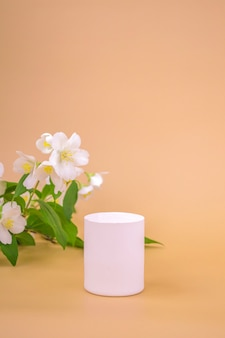 Round high podium to showcase cosmetics, products on a beige background and jasmine