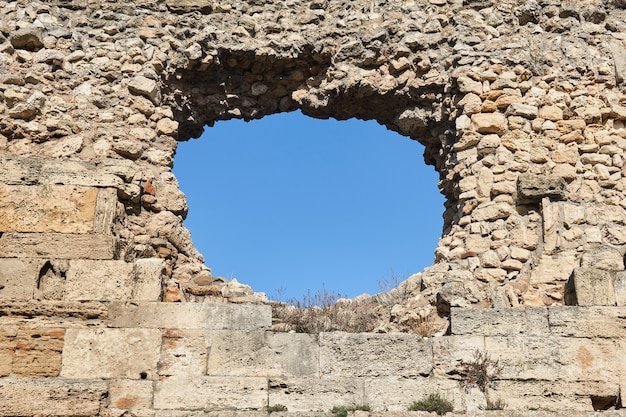 Round hole in the old medieval fortress wall through which the sky can be seen