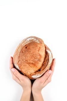 孤立した背景に、手で丸い自家製パン