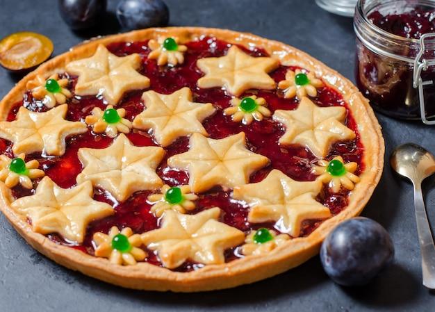 Round homemade cake with plum jam, plums.