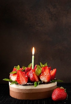 Round homemade chocolate cake with fresh strawberries and mint and with burning holiday candle, close-up