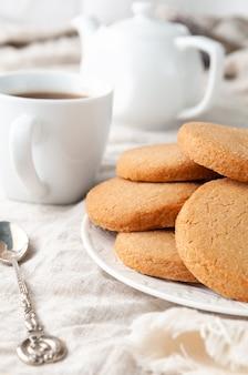 自家製の丸いショートブレッド クッキー。白いお皿に。グレーのリネンのテーブルクロスに。背景には、クッキーのスタックがあります。白いティーポットとマグカップ。
