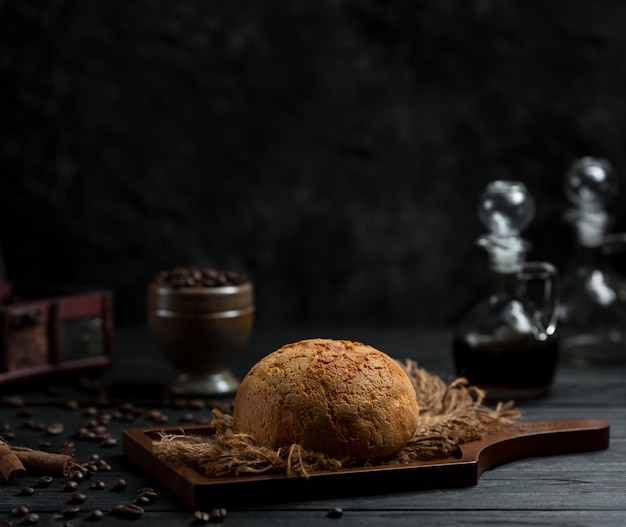 Round homemae bread bun pn a wooden board in a very dark space