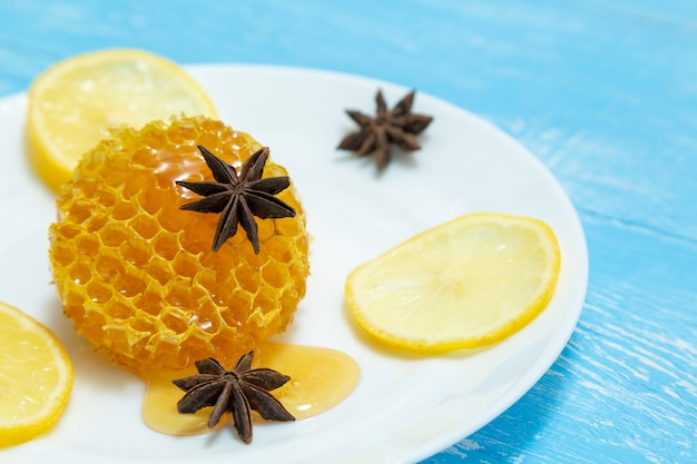 Round honeycombs, lemon and anise lie on a plate on a blue .
