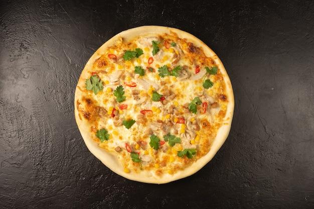 マグロ、オリーブ、ディル、チーズを添えた丸い焼きたてのピザが黒い石のキッチンテーブルの上にあります