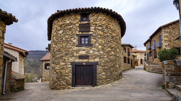 Round house made of piece with wooden door and window located in old medieval village. horcajuelo madrid. madrid.