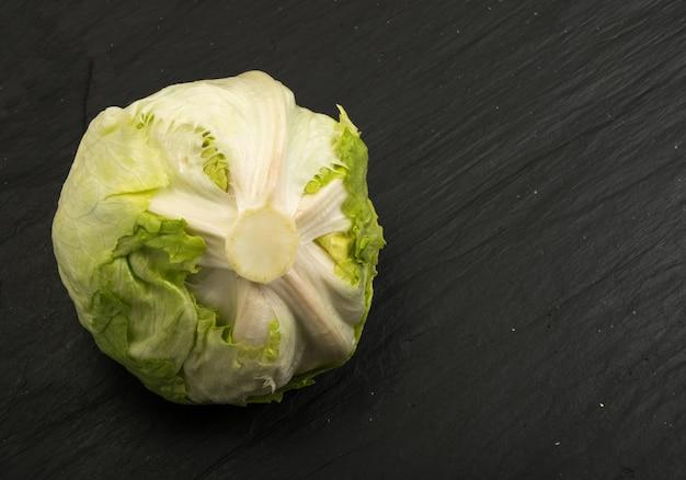 Round iceberg lettuce on black stone background.