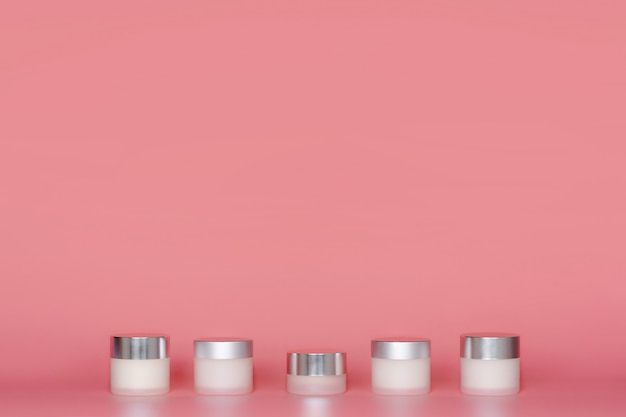 Round jars of cosmetic cream standing on pink background.