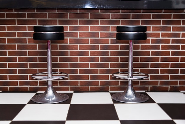 Round leather chairs stand near the bar counter