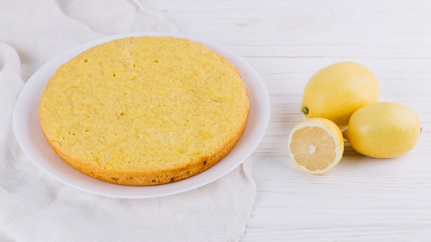 Round lemon cake served in white plate with whole lemons on wooden backdrop