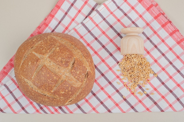テーブルクロスにオーツ麦の穀物とパンの丸いパン