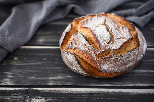 焼きたてのサワードウパンの丸いパン。暗いテーブルの上の職人のパン。素朴なサワー種のパン。