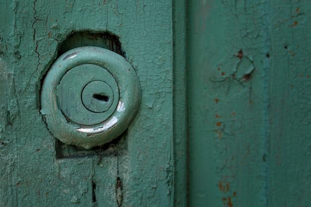 오래 된 푸른 나무 문에 둥근 자물쇠입니다. 확대.