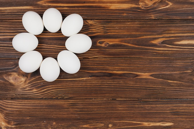 Round made from white eggs on wooden table