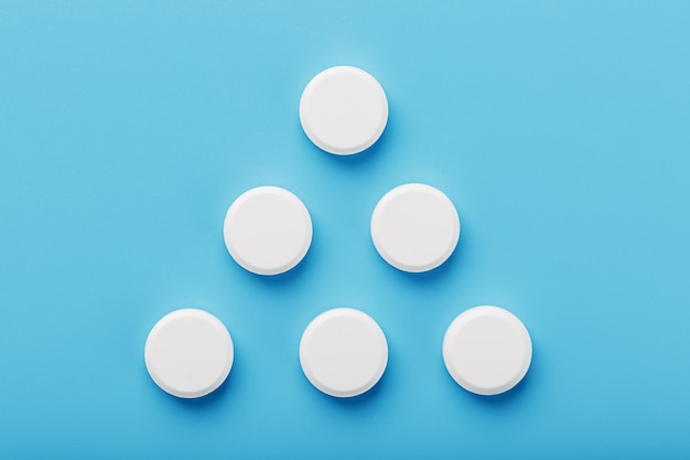 Round medicinal tablets in the shape of a triangle on blue