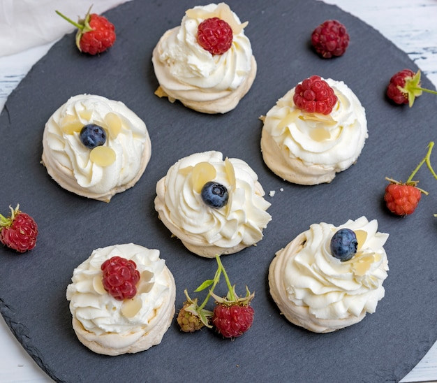 Round meringues with whipped cream on a black graphite board