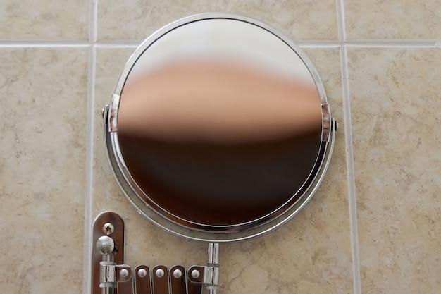 壁に取り付けられたバスルームの丸い鏡。閉じる