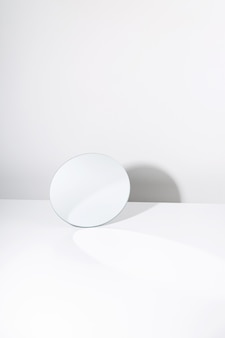 Круглое зеркало на белом столе с теневым минимализмом Premium Фотографии