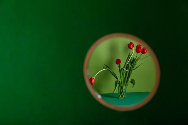 Круглое зеркало с отражением цветка на зеленом фоне