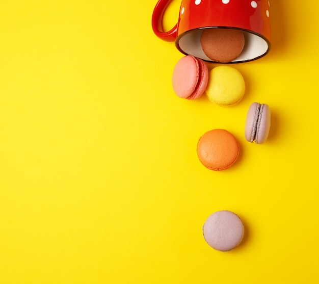 Round multicolored macarons falling from a red ceramic cup