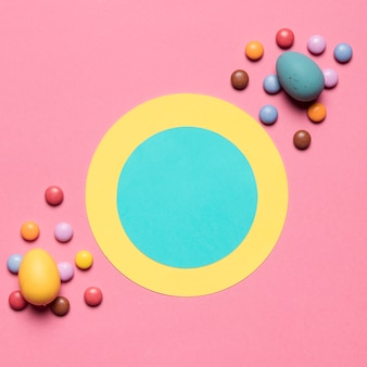 Round paper frame decorated with gem candies and easter eggs on pink background
