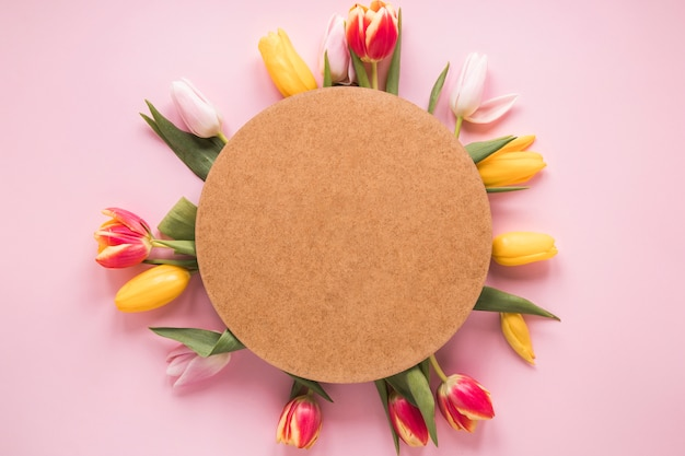 Round paper on tulip flowers on table