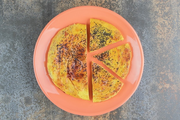 Round pastry with poppy seeds on an orange plate