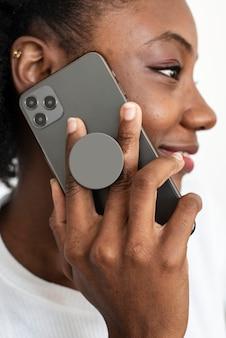 アフリカ系アメリカ人の女性が電話で話している携帯電話の後ろの丸い電話グリップ