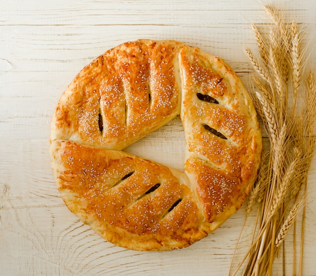Round pie with sesame seeds, ears of wheat
