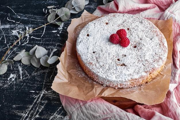 Una torta tonda con zucchero a velo e lamponi.