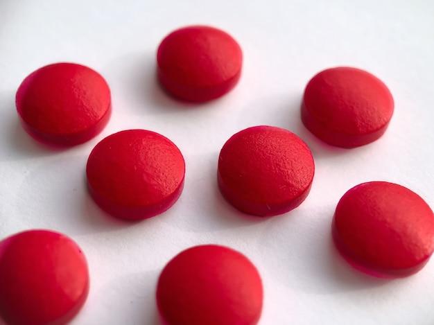Круглые таблетки красного цвета, изолированные на белом фоне. концепция здоровья.