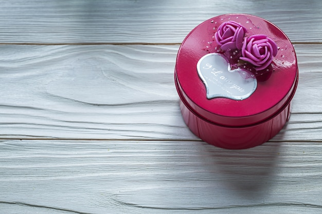 Round pink gift box with roses on wooden board celebrations concept
