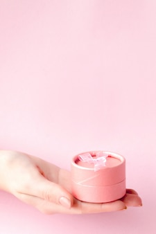 Round pink gift box in women's hands on a pink background. festive concept for valentine's day, mother's day or birthday